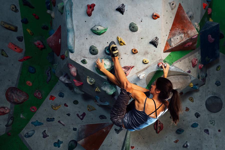 Mädchen übt Heelhook in einer Session ihres Klettertrainings.