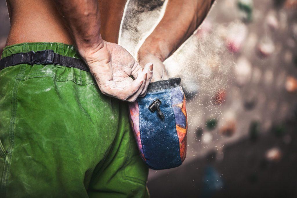 Mann verteilt Chalk auf den Händen beim Bouldern.