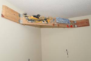 Ein Hangboard mittels Holzbrett in einer Ecke angebracht.