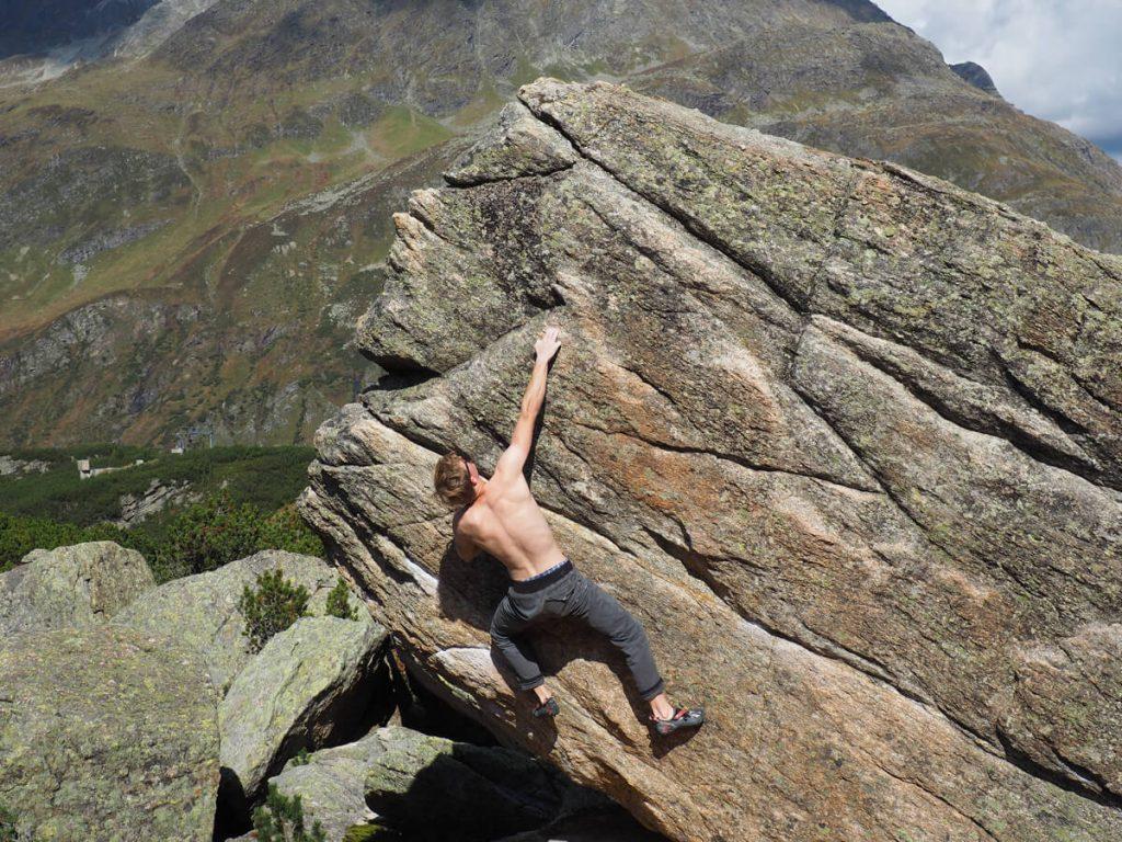 Boulderer klettert an gut sichtbaren Chalkspuren an Fels im Gebiet Silvretta